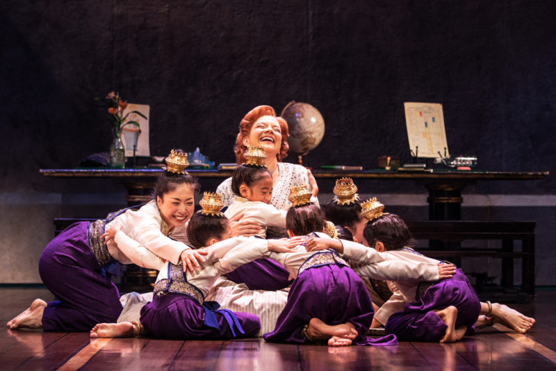 Anna in hoop skirt sits on the floor surrounded by the King of Siam's children.