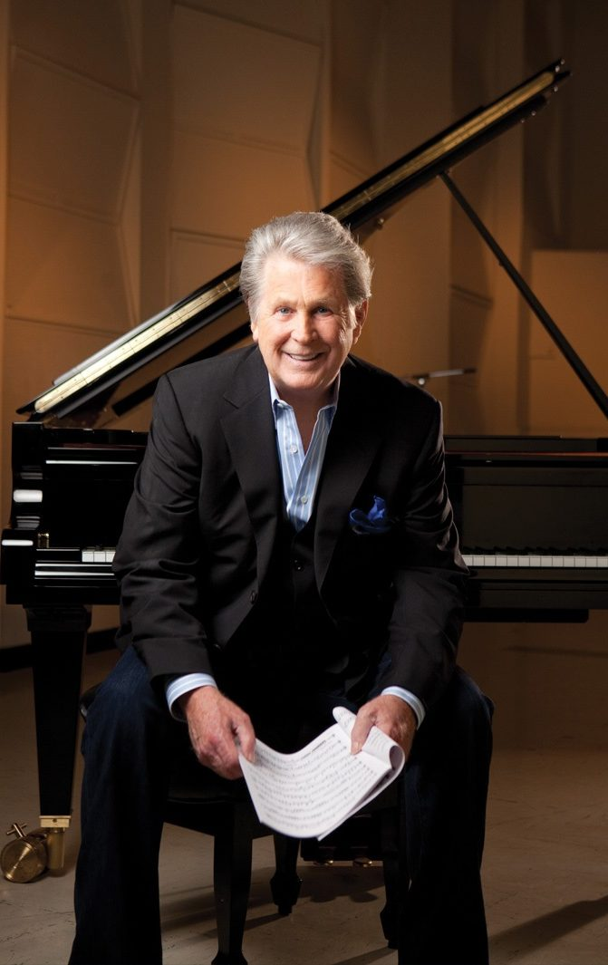 Brian Wilson sits on a piano bench