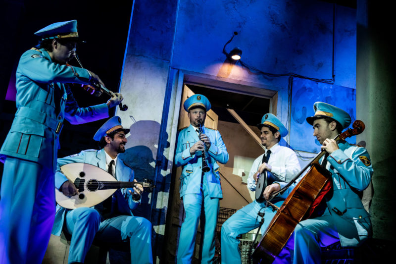 Five musicians play their instruments dressed in the uniforms of the Alexandria Ceremonial Police Orchestra.