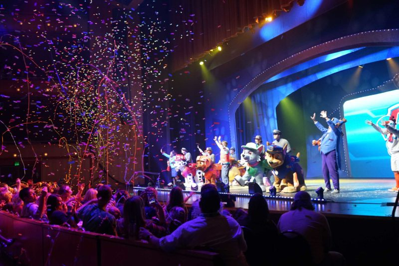 """The cast of PAW Patrol Live! """"Race to the Rescue"""" on stage during a performance while confetti rains down over the audience visible in the photo."""