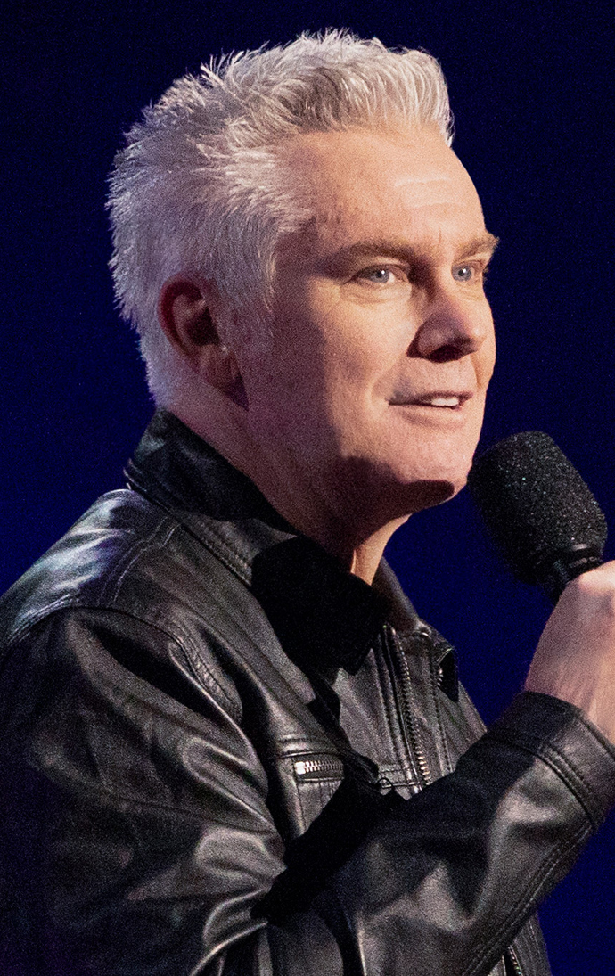 brian regan in black leather jacket with mic in hand