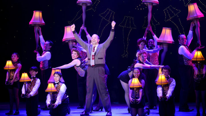 A middle aged man dressed in a cardigan, loudly patterned red tie, dress shirt and slacks stands center stage triumphant with arms raised above his head. The company of A Christmas story surrounds him holding leg lamps of all sizes while wearing glittery vests, bow ties, and slacks.