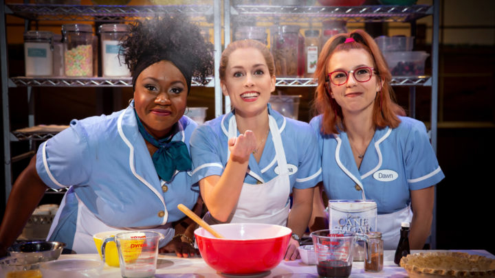 A black woman with a neckerchief and natural hair pulled back, a white woman with strawberry blonde hair pulled back into a pony tail, and a white woman with a red high ponytail look on at a puff of flour in mid air. They are all wearing waitress uniforms.