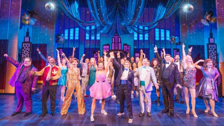 The company of The Prom on Broadway pose at the end of the show's finale with one arm outstretched above their head while dressed in their finest duds in a high school gym at the prom